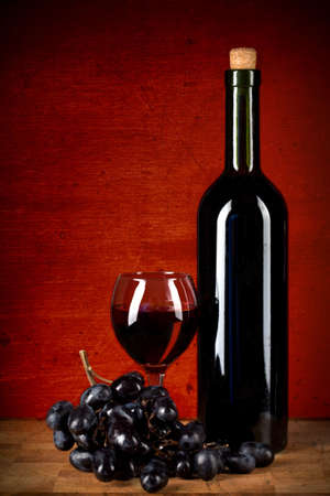 bottle of wine, glass and grapes over red  grunge background photo