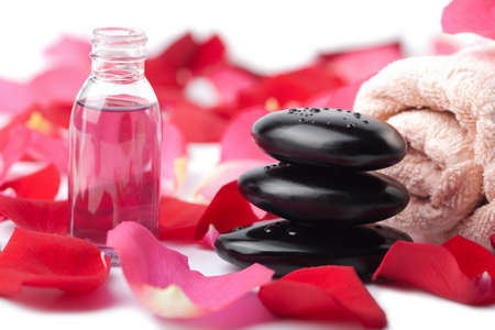 zen stones, essential oil and rose petals isolated photo