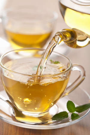 green tea pouring into glass cup Stock Photo