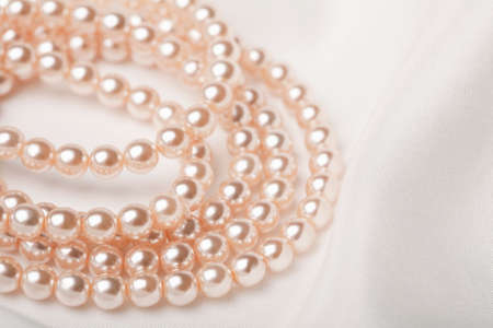 pearl necklace over white silk photo