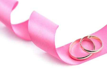 Golden wedding rings over pink ribbon isolated photo
