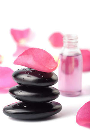 spa stones, essential oil and rose petals isolated photo