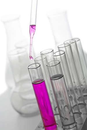líquido goteando de pipeta en tubo de ensayo aislado  Foto de archivo