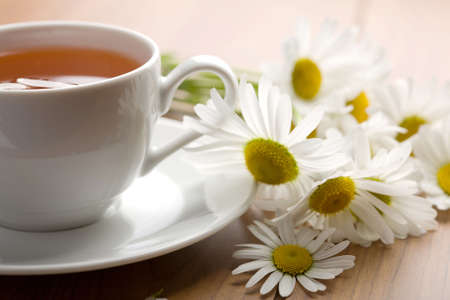 camomiles: white cup of herbal tea and camomile flowers