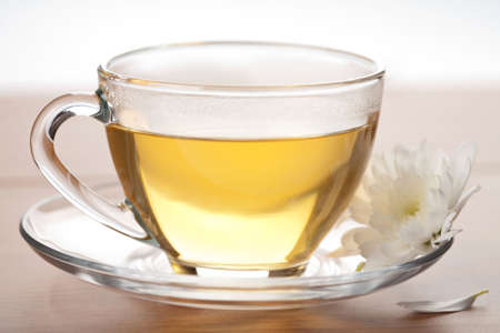 cup of green tea and white flower