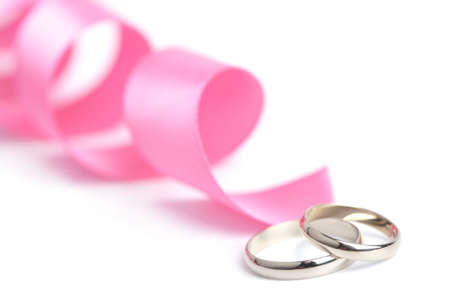 Gold wedding rings and pink ribbon isolated photo