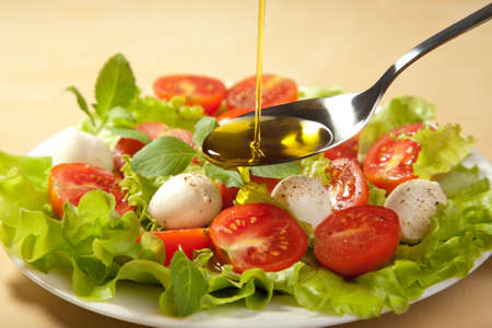 olive oil pouring over salad photo