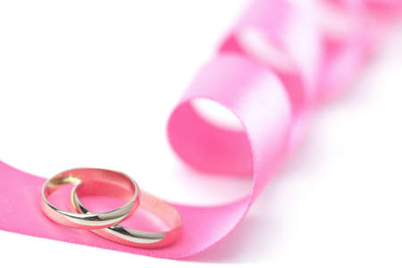 Gold wedding rings over pink ribbon isolated  photo