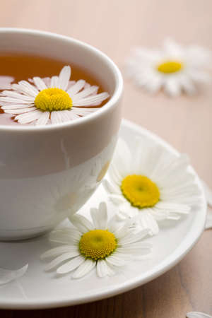 cup of herbal tea and chamomile flowers photo