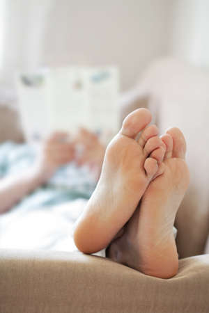 feet in bed: man relaxing on sofa. focus on feet