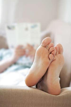 bare feet: man relaxing on sofa. focus on feet