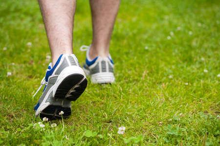 スニーカー: 草の上の人間の歩行の脚