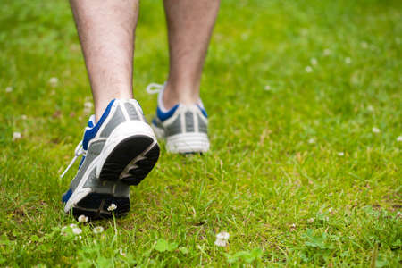 sneakers: legs of walking man on grass
