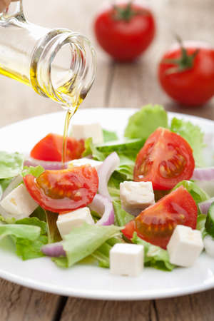 oil pouring over fresh salad  photo