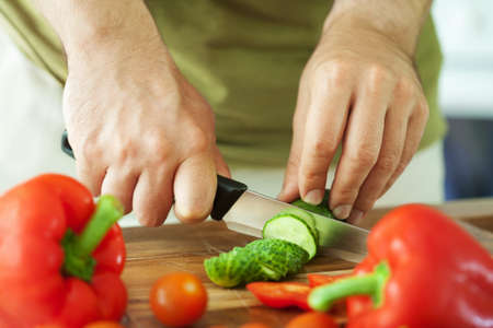 cutting vegetables: man cutting vegetables for salad Stock Photo