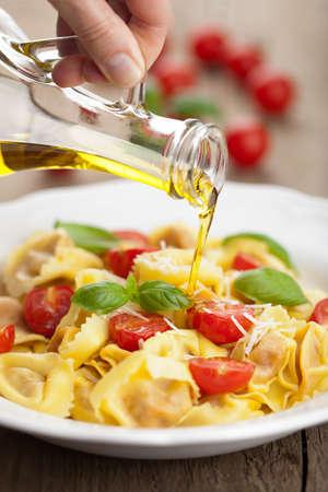 aceite de cocina: aceite de oliva que vierte sobre tortellini de queso y tomates Foto de archivo