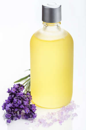 etherische olie en lavendel bloemen in wit Stockfoto