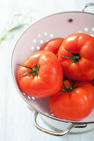 a colander: fresh beef tomatoes in colander Stock Photo
