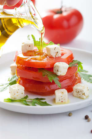 olive  oil: pouring olive oil over salad with beef tomatoes and feta
