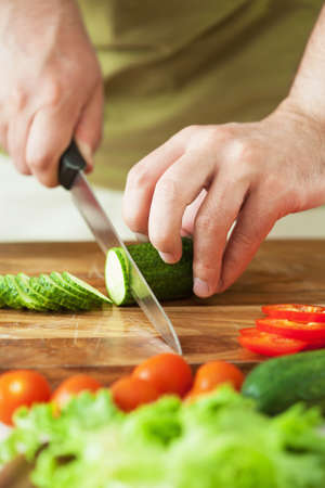 man cutting vegetables for salad  photo