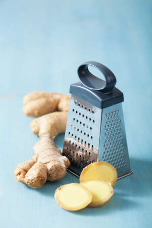 metal grater: fresh ginger root and grater over blue  Stock Photo