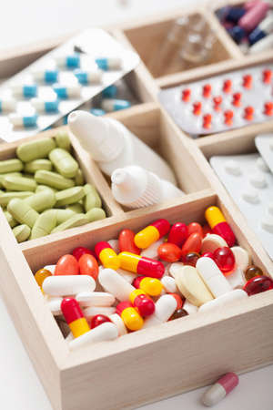 medical pills and ampules in wooden box photo