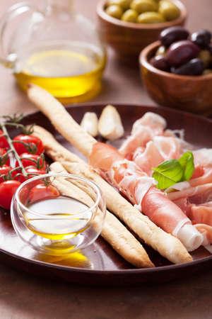 grissini: italian prosciutto ham grissini bread sticks tomato olive oil Stock Photo