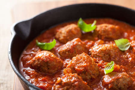 black dish: meatballs with tomato sauce in black pan