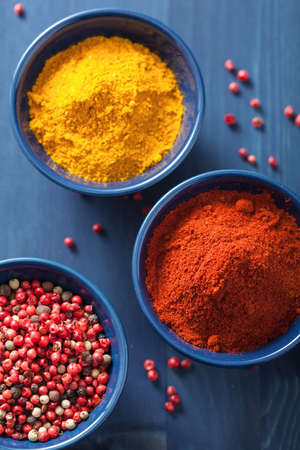 curry powder: spices in bowls: curry pink and black pepper paprika powder Stock Photo