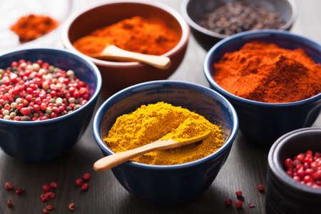 curry powder: spices in bowls: curry, pink and black pepper, paprika powder