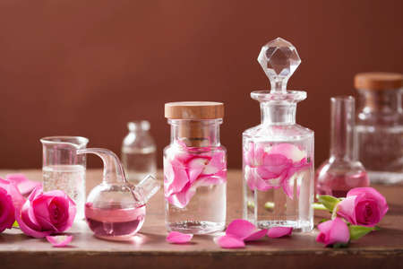 alchemy and aromatherapy set with rose flowers and flasks
