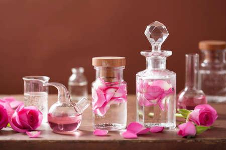 destilacion: alquimia y set de aromaterapia con flores de rosa y frascos Foto de archivo