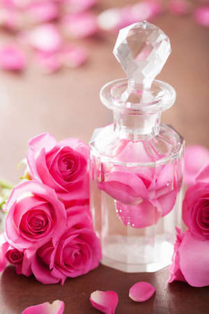 perfume bottle and pink rose flowers  spa aromatherapy  Stockfoto