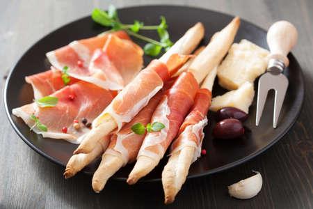 jamones: jamón prosciutto y palitos de pan grisines. antipasto italiano Foto de archivo