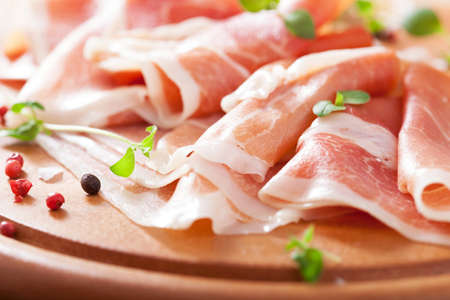 sliced prosciutto ham on chopping board with oregano and pepper photo