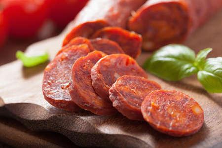 chorizo: spanish chorizo sausage with basil on chopping board