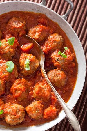 gehaktballetjes met tomatensaus in de pan met lepel