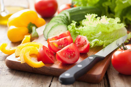 cutting vegetables: fresh vegetables cucumber tomatoes pepper and salad leaves