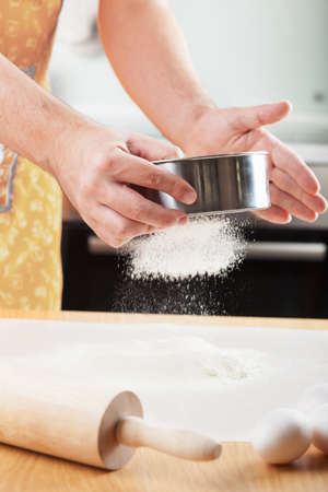 sift: mans hands sifting flour through a sieve for baking