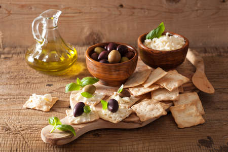 crackers with soft cheese and olives photo