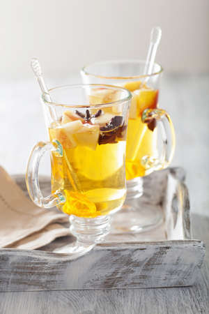 mulled: glass of mulled apple cider with  orange and spices, winter drink