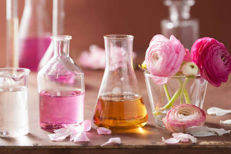 aromatherapy: alchemy and aromatherapy set with ranunculus flowers and flasks