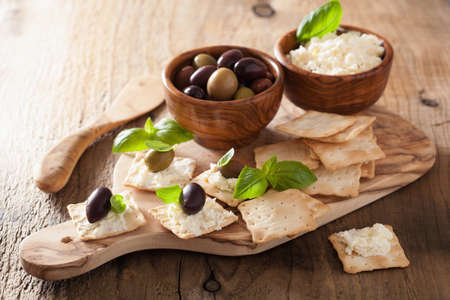 crackers with soft cheese and olives. healthy appetizer photo