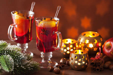 grog: glass of mulled wine with orange and spices, christmas decoration background