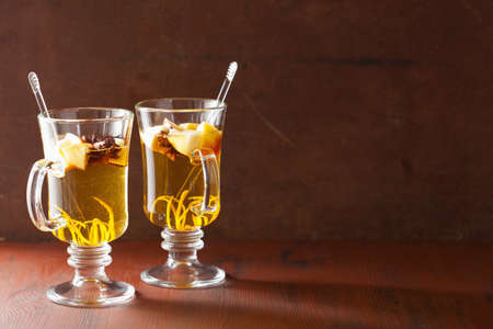spiced: glass of mulled apple cider with orange and spices, winter drink background