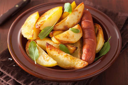 wedges: baked potato wedges and sausage in plate over brown rustic table Stock Photo
