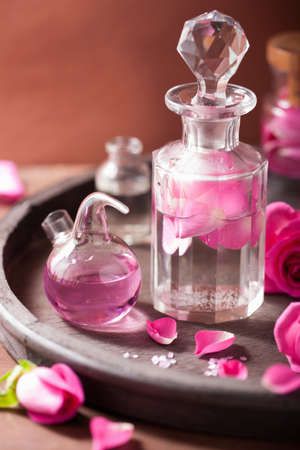 alchemy and aromatherapy set with rose flowers and flasks photo