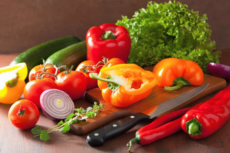 knife tomato: chopping healthy vegetables pepper tomato salad onion chilli on rustic background Stock Photo
