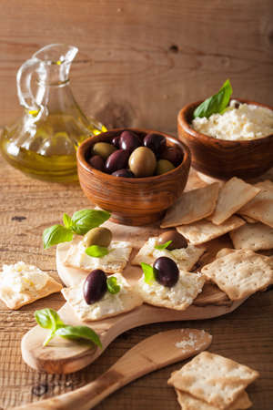 kalamata: crackers with soft cheese and olives. healthy appetizer