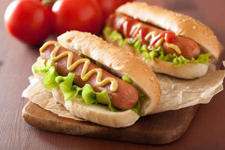 perro caliente: perrito caliente con mostaza salsa de tomate y lechuga Foto de archivo